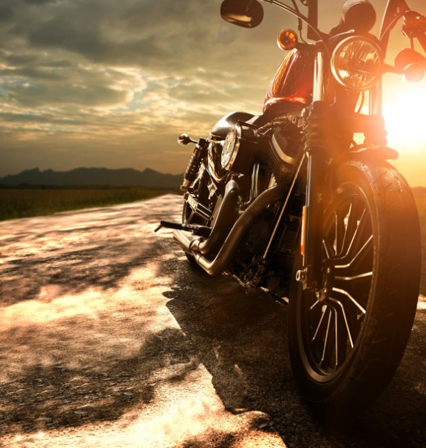 old-retro-motorcycle-traveling-on-country-road-against-beautiful-light-of-sunset-sky_34013-284